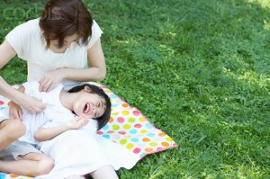 Mother Tickling Son Outdoors